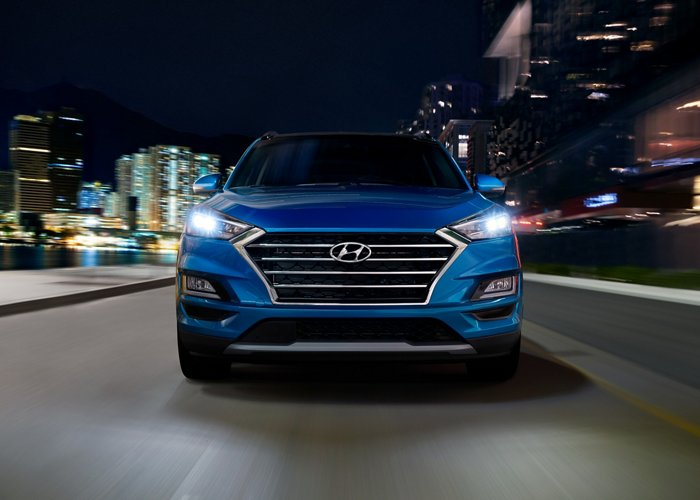 Front grille of a blue 2020 Hyundai Tucson on a highway at night