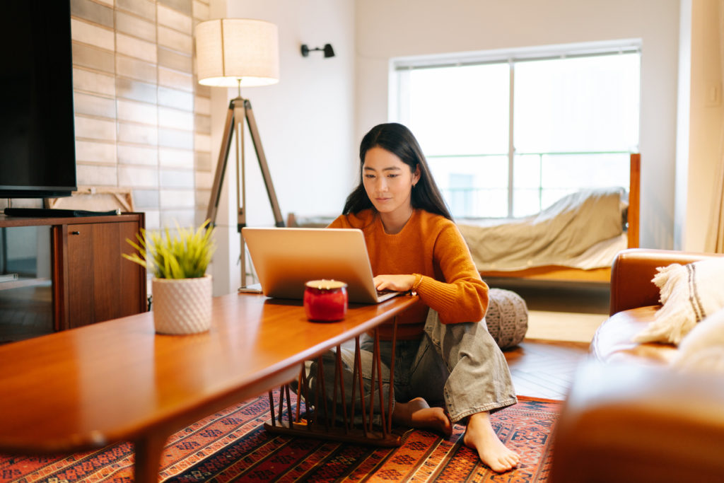 Young woman using laptop comfortably at home.