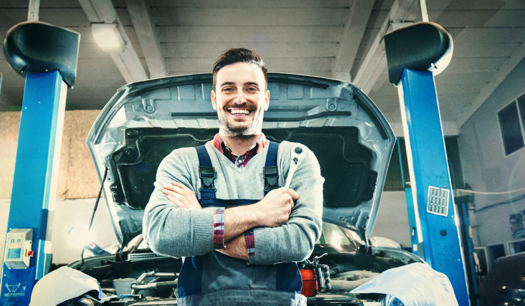 Smiling service technician standing in front of a car in his shop