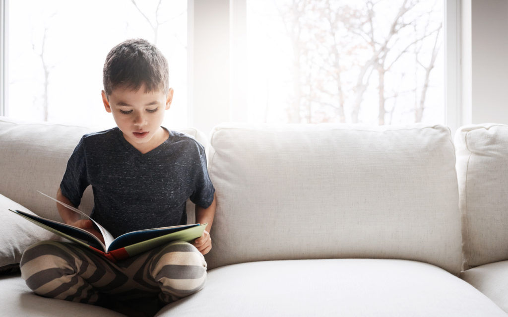 Child reading a book on the couch