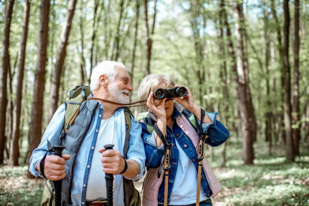 Senior couple bird watching on a hike