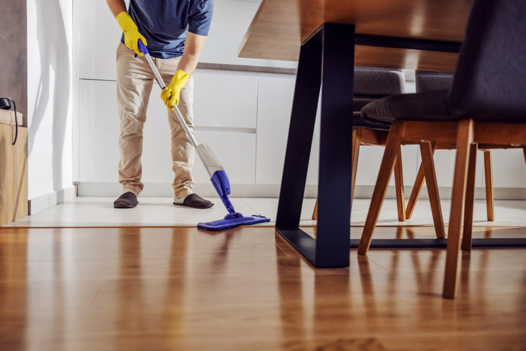 Cropped picture of tidy young man with rubber gloves cleaning kitchen floor with mop.