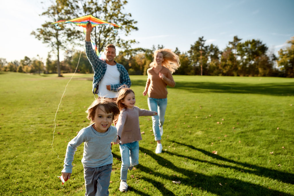 Family of four flying a kite at a park
