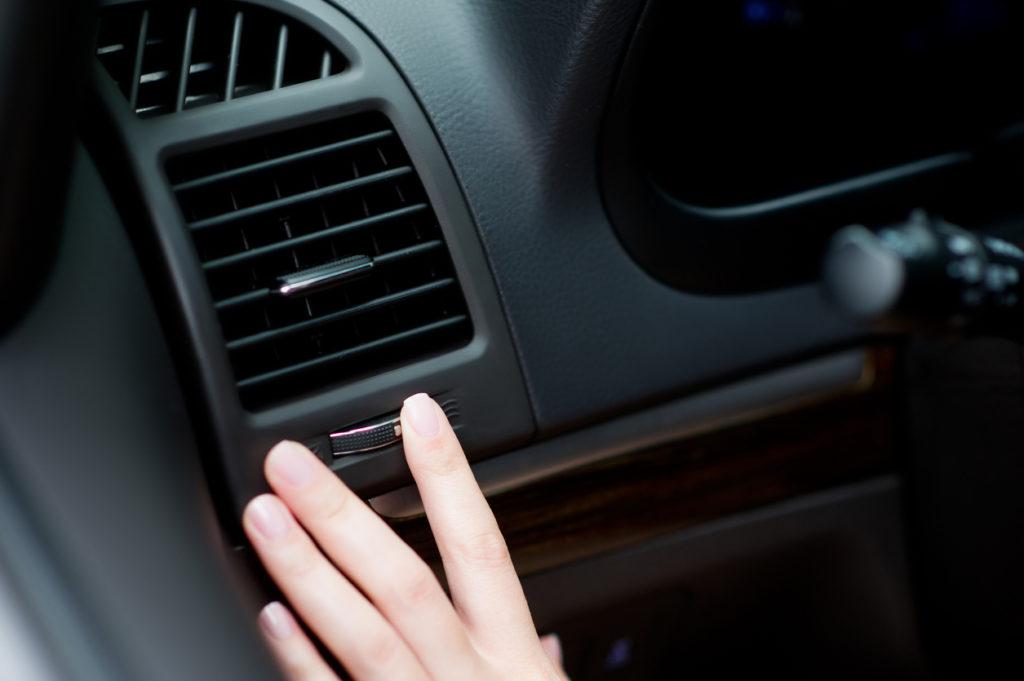 Driver adjusting air vent in car