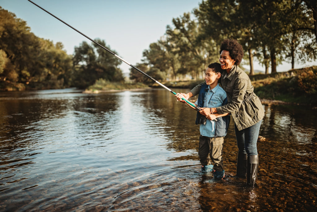 Mother teaching her son how to catch a fish