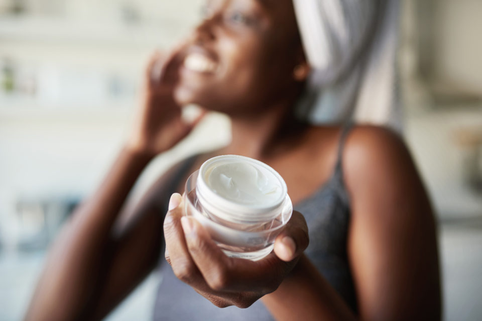 Photo of woman applying moisturizer to her face.