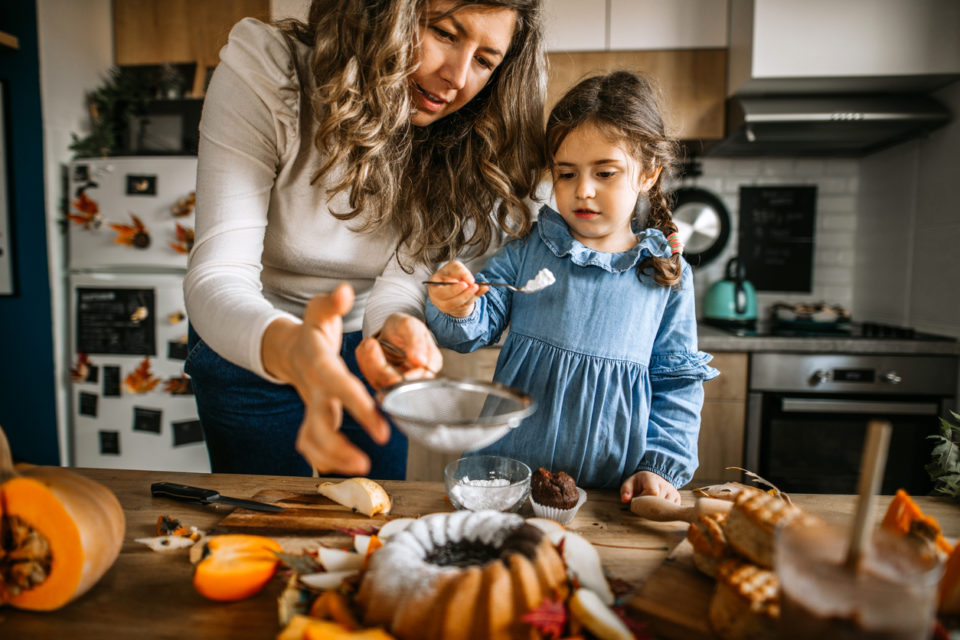 Mother and her little cute daughter are dusting cake